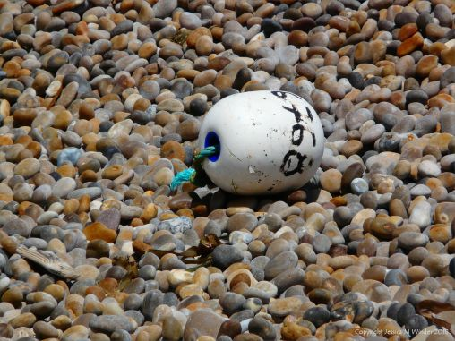 White fishing buoy washed up on a pebble shore