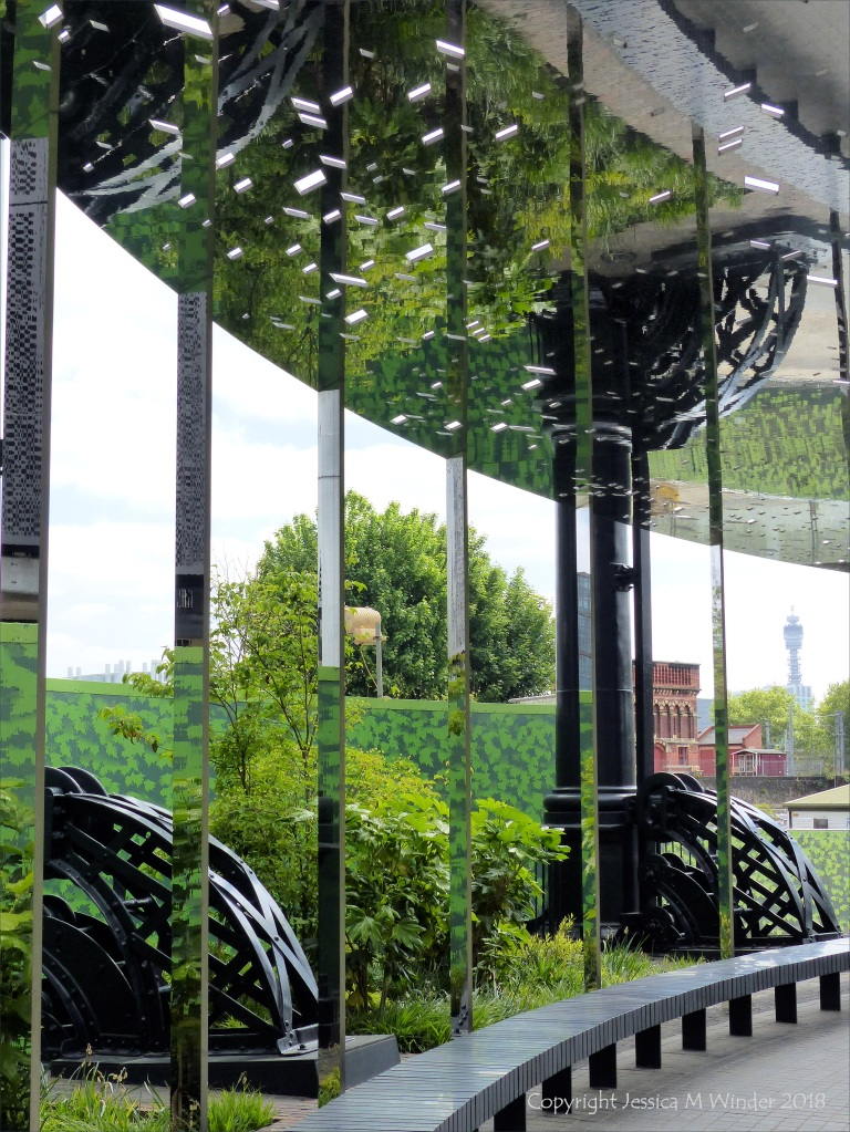 A circular mirrored garden in the structural framework of an old gasometer