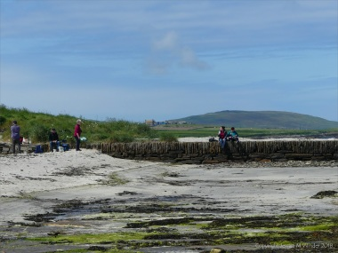 People picnicking on an old stone pier at Grit Ness