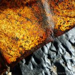 Rusty metal debris on the beach below the Spittles at Lyme Regis