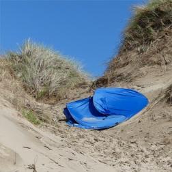 Blue pop-up tent blown into the beach dunes