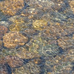 Natural patterns of reflected light on water flowing over pebbles
