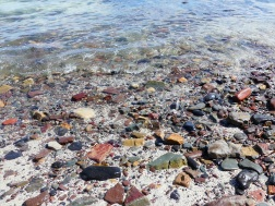 The water's edge with beach stones and sand