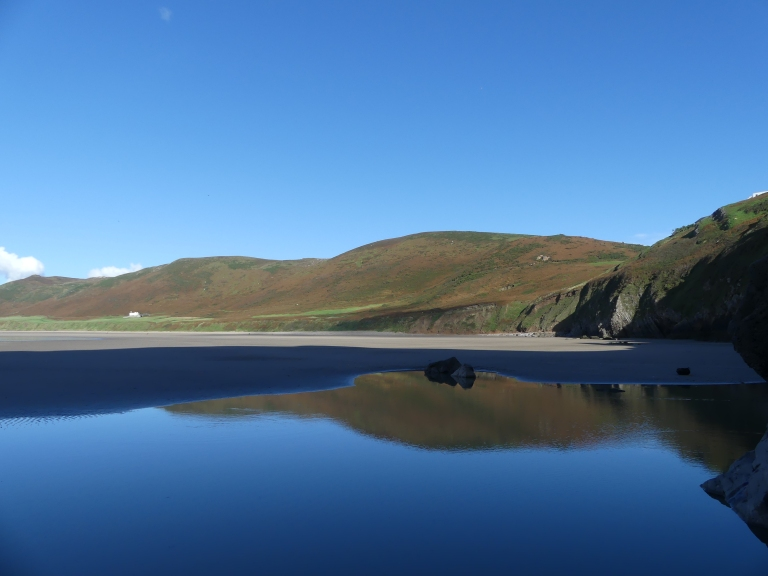 Reflection of Rhossili Down in  tide pool on the beach