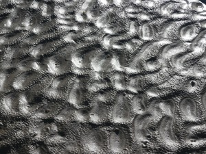 Natural patterns in wet beach sand pitted by rain drops