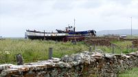 Stone walls and old boats near Stromness