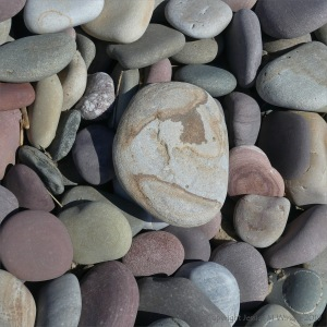 Pastel coloured dry pebbles on the beach