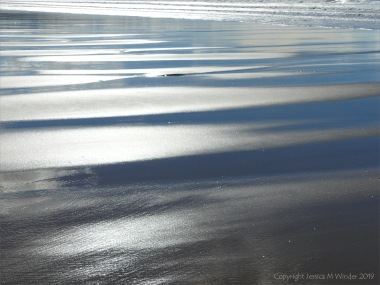 Wet sand gleaming in sunlight