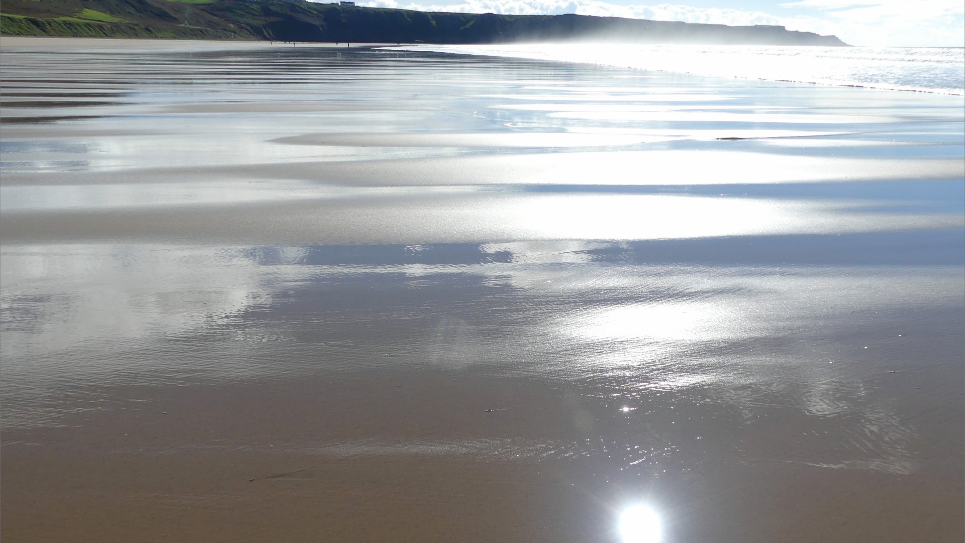 Wet sand gleaming in sunlight