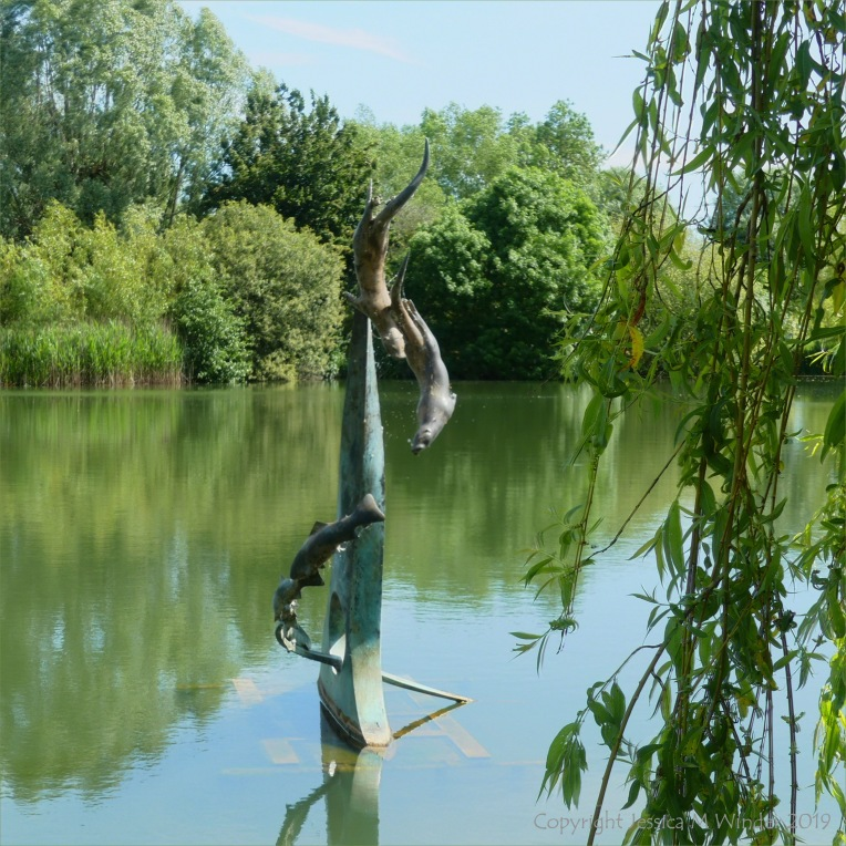 """""""The Chase"""" bronze sculpture in a lake"""