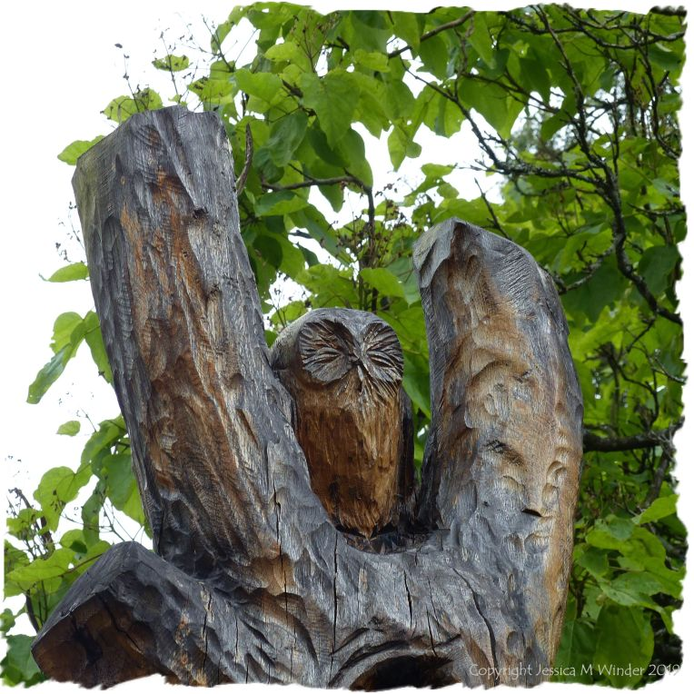 Carved owl against the tree top