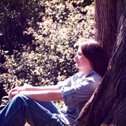 Woman sitting against a redwood tree