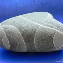 Pebble with pattern of white lines