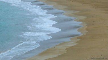 Waves gently breaking on a sandy beach