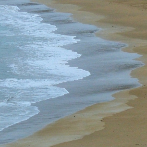 Waves gently breaking on a sandy beach