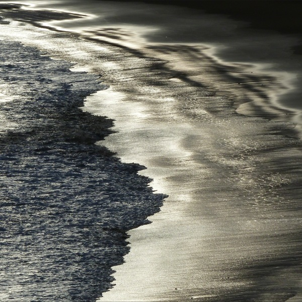 Beachscape with reflected dawn light on the sea