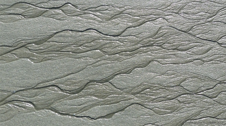 Natural patterns in the sand on a beach as the tide goes out