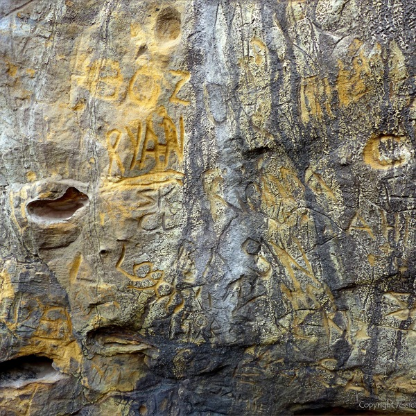 Graffiti carved into natural rock face