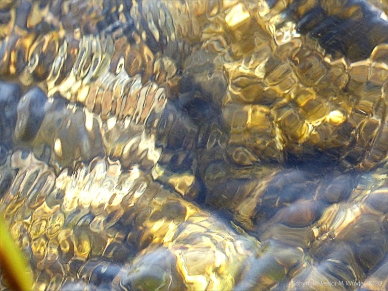 Abstract natural patterns of reflected light on flowing rippled water