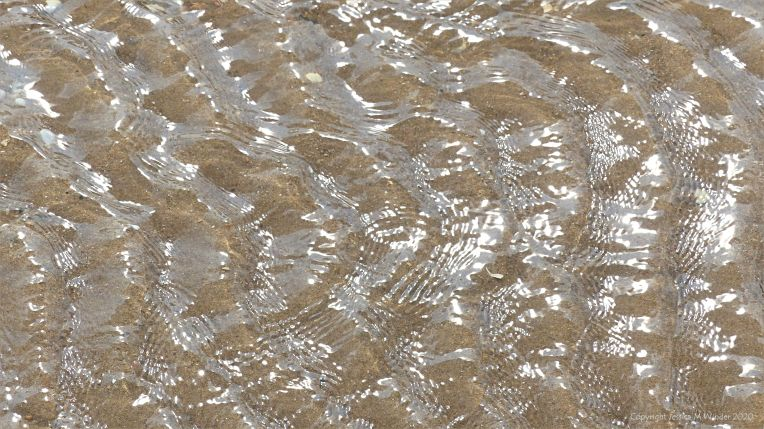 Rippled water of a beach stream at Swansea Bay