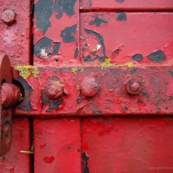 Flaking red paint on a piece of wooden agricultural equipment