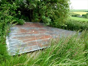 Sheet of corrugated iron from a collapsed roof of a farm outbuilding in the fields