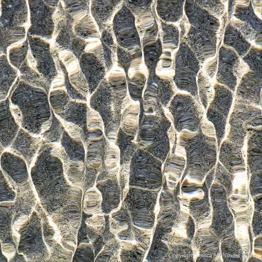 Refracted light on shallow tide pool rippled water