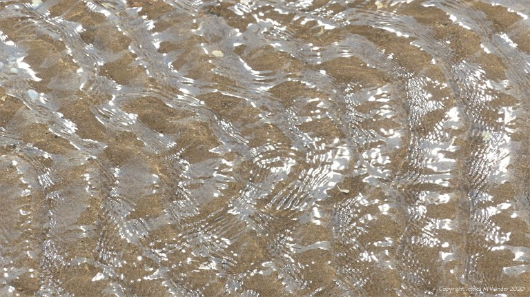 Patterns of reflected light on the surface of rippled water