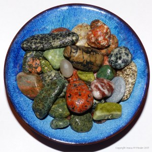 Brightly coloured pebbles in a blue bowl