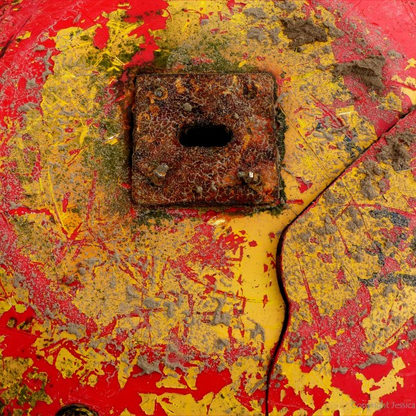 Close-up detail of red buoy washed up on sandy beach as flotsam