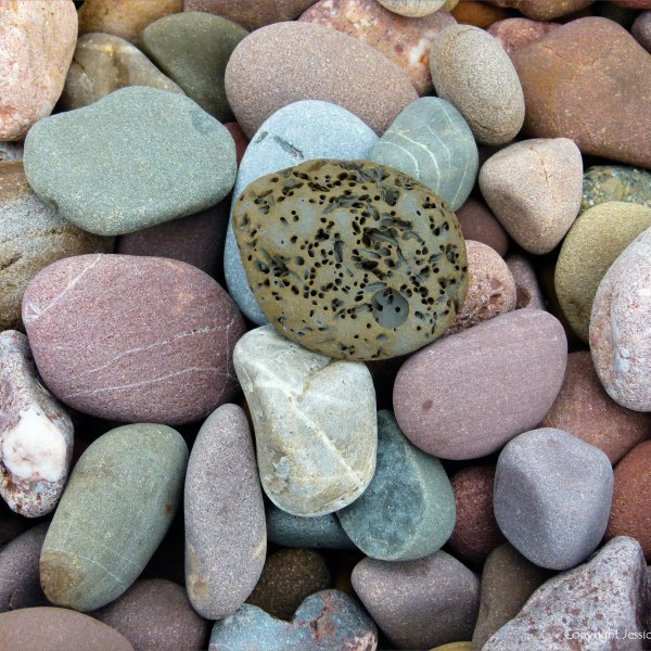 Large pebbles of different rock types on the beach