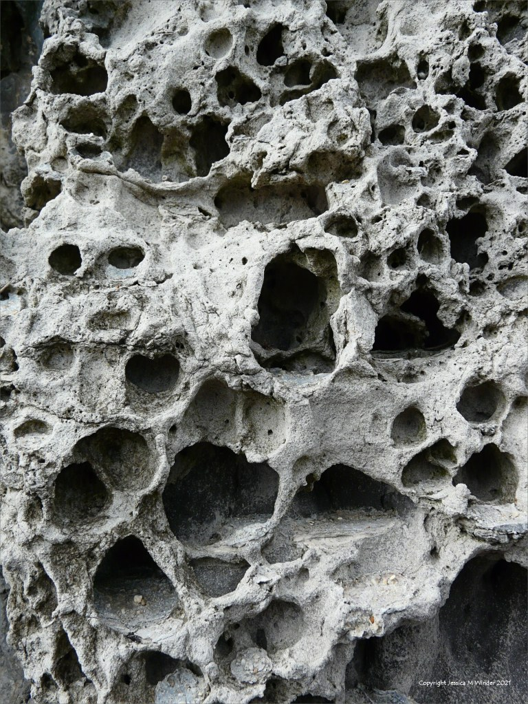 Rock with holes caused by natural erosion in a sea wall