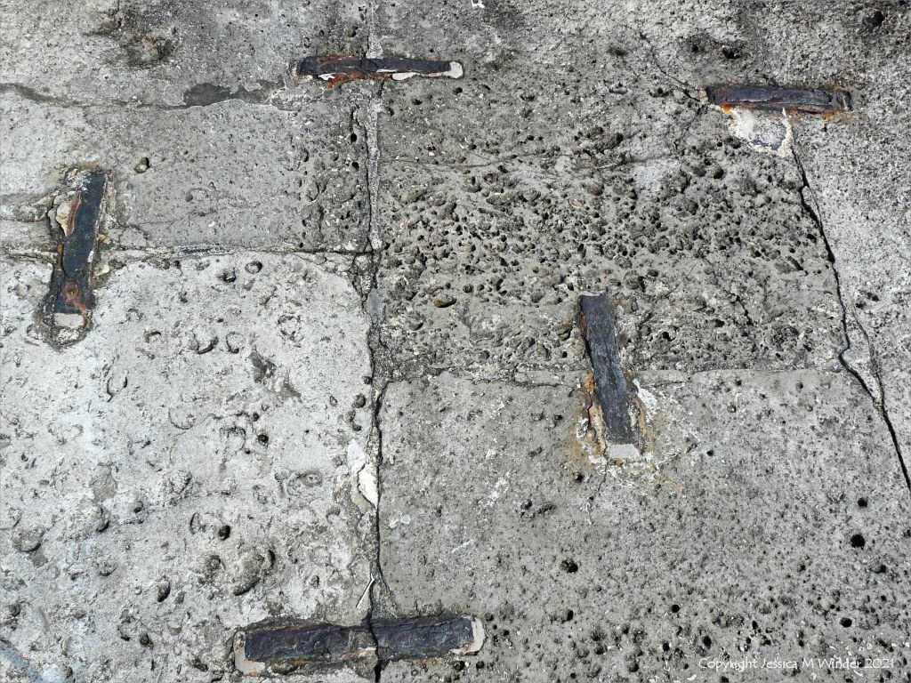 Stone blocks in a sea wall with shaped holes left by erosion of shell fossils